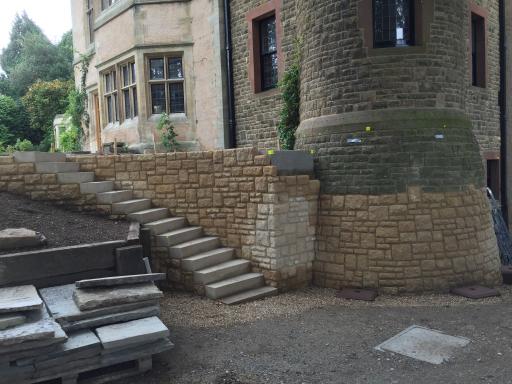 Wimbledon garden featuring coursed-rubble walling in Doulting limestone, York stone steps and St Bees Sandstone pad stones